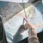 Finger pointing to an open map in car